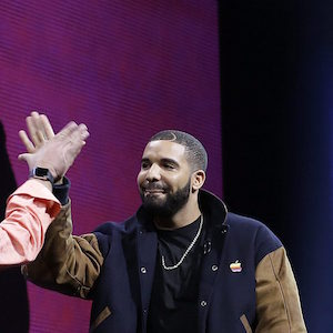 Musician Drake, right, high fives Eddy Cue, Apple senior vice president of Internet Software and Services, during the Apple Worldwide Developers Conference in San Francisco, Monday, June 8, 2015. The maker of iPods and iPhones announced Apple Music, an app that combines Beats 1, a 24-hour, seven-day live radio station, with an on-demand music streaming service. (AP Photo/Jeff Chiu)