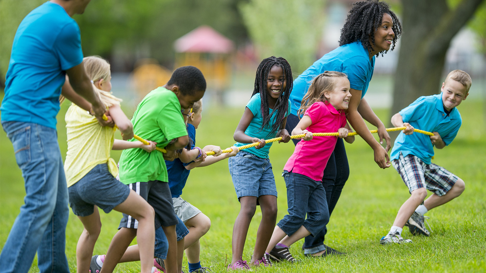 Kids and counselors playing tug of war at summer camp. (FatCamera/iStock)