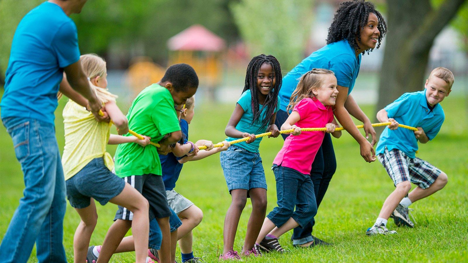 Kids and counselors playing tug of war at summer camp. (FatCamera/iStock)