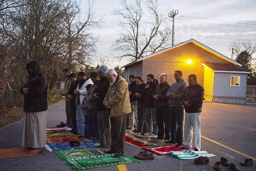 Congregation members hold prayer in the parking lot, on Sunday, November 15, 2015, after the only mosque in Peterborough, Ont., was deliberately set alight Saturday night. (THE CANADIAN PRESS/Christopher Katsarov)