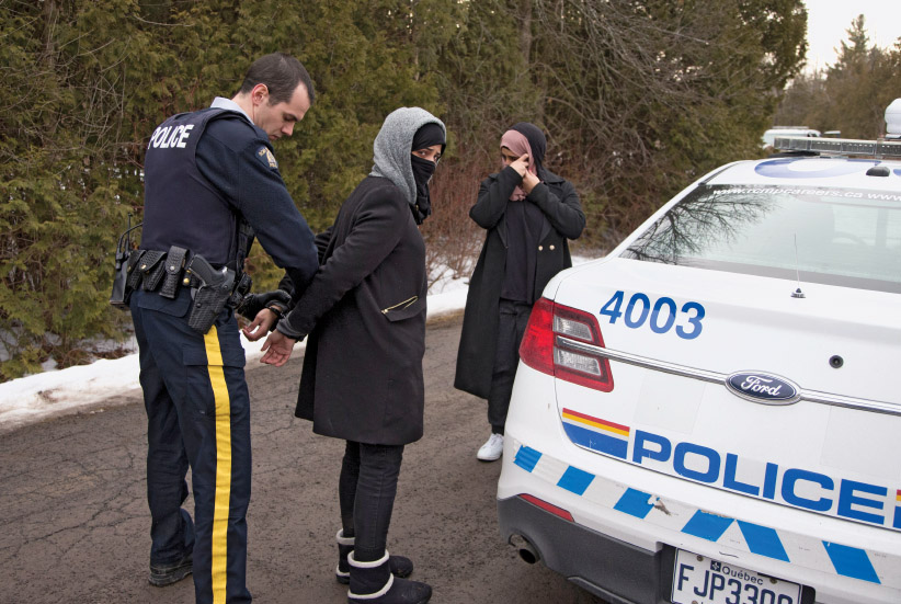 Two women claiming to be from Yemen are detained by a Royal Canadian Mounted Police (RCMP) officer after crossing the U.S.-Canada border into Hemmingford, Quebec on February 22, 2017.  (Christinne Muschi/Reuters)