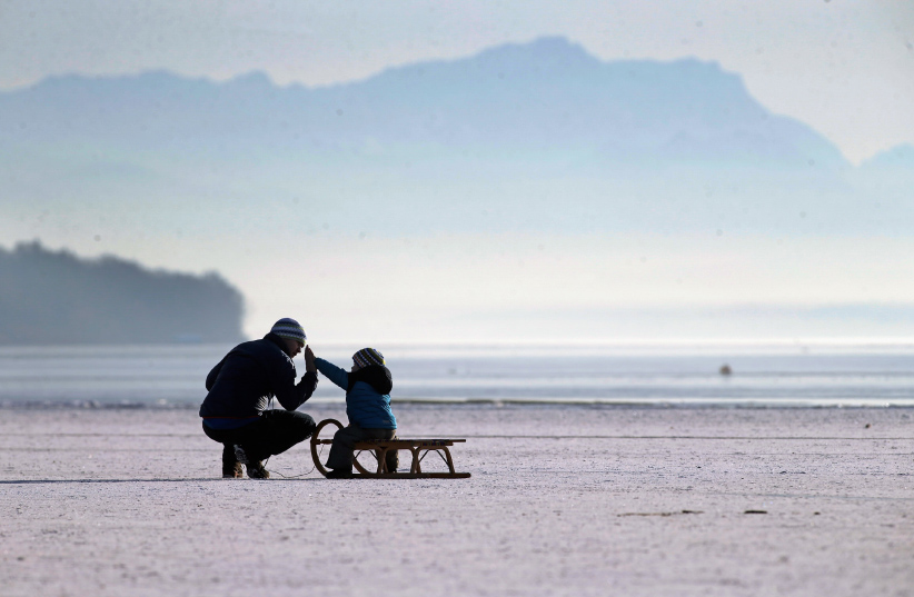 A father and his child enjoy walking on Lake Ammersee on January 28, 2017 in Stegen am Ammersee, Germany. After an unusual cold winter period currently most of the Bavarian lakes are completely or partly frozen. (Johannes Simon/Getty Images)