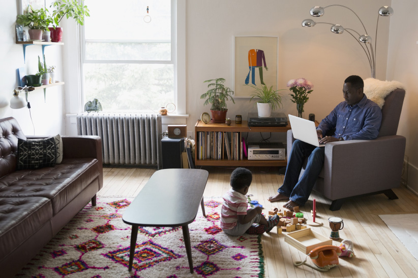 Father using laptop near son playing with toys in living room. (Hero Images/Getty Images)