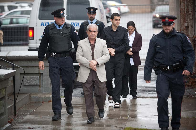 Mohammad Shafia (l), eldest son Hamed Shafia and Tooba Mohammad Yahya ( back) exit a police van and are escorted to the Kingston Courthouse on Monday December 5, 2011. He along with his dad and mother are accused of killing the teenage Shafia sisters and Shafia's first wife in a polygamous marriage over family honour. (Photograph by Vincenzo D'Alto)