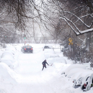A woman shovels snow from around her car following a winter storm in Montreal, Wednesday, March 15, 2017. (Graham Hughes/CP)