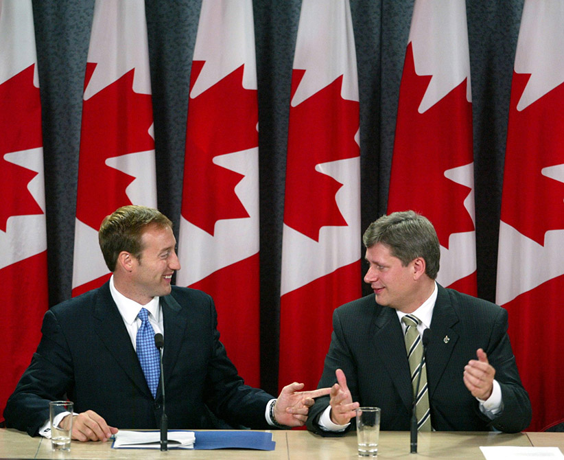 Progressive Conservative leader Peter MacKay (left) and Canadian Alliance leader Stephen Harper address the media at a news conference announcing a merger deal with the two parties, in Ottawa Thursday Oct 16, 2003. (Jonathan Hayward/CP)