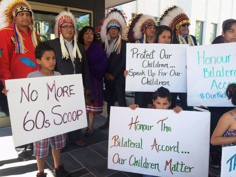 Children hold signs along with members of the Saskatoon Tribal Council outside of the courthouse in Regina Sask., on Tuesday, June 28, 2016. The Saskatchewan government is seeking an injunction to take back responsibility for children under the care of the Saskatoon Tribal Council, but some say the move infringes on aboriginal sovereignty. (Jennifer Graham/CP)