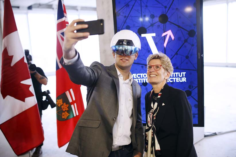 Kathleen Wynne, premier of Ontario, right, poses for a selfie photograph with a man wearing a virtual reality (VR) helmet in the Vector Institute at the MaRS Discovery District in Toronto, Ontario, Canada, on Thursday, March 30, 2017. A new institute for artificial intelligence research opened Thursday with funding from the federal and Ontario governments as well as the private sector. The Vector Institute will specialize in the fields of machine learning and deep learning, which uses software and algorithms to simulate the neural circuits of the human brain. (Cole Burston/Bloomberg/Getty Images)