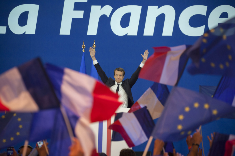 French presidential election candidate for the En Marche ! movement Emmanuel Macron raises his hands as he arrives on stage to deliver a speech at the Parc des Expositions in Paris, on April 23, 2017, after the first round of the Presidential election. (Stéphane Rouppert/CP)