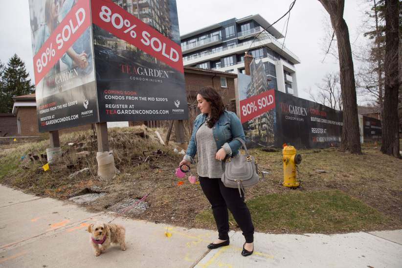 Stephanie Fusco, who is currently renting and looking to buy with her husband but has been having a hard time finding a place despite the many real estate signs in her neighborhood, takes her dog Chloe for a walk in Toronto on April 5, 2017. (Photograph by Michelle Siu)