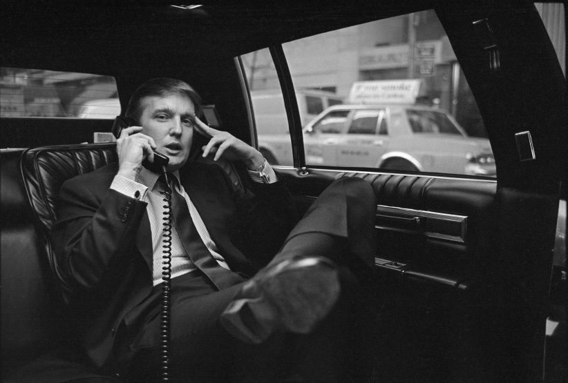 Donald Trump on the phone in his car after announcing plans for development of the west side of midtown Manhattan at the Hyatt Hotel on 42nd Street and Lexington Avenue, in New York, NY, November 18, 1985. (Neal Boenzi/The New York Times/Redux)