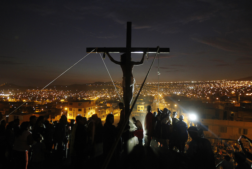 An actor playing the role of Jesus Christ hangs from a cross during the re-enactment of the crucifixion of Jesus Christ during Holy Week at Mi Peru, a shanty town on the outskirts of Lima April 17, 2014. REUTERS/Enrique Castro-Mendivil