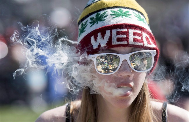 A woman exhales while smoking a joint during the annual 420 marijuana rally on Parliament hill on Wednesday, April 20, 2016 in Ottawa. Some teens say their likelihood of using weed hasn't changed since the Liberal government announced details of its legalization plan - though they say it's made them more aware of information on both sides of the debate.THE CANADIAN PRESS/Justin Tang