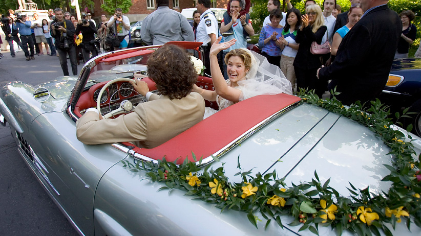 New bride Sophie Gregoire waves to the crowds with her husband Justin Trudeau, son of the late Prime Minister Pierre Elliot Trudeau, as they drive off in his father's refurbished 1959 Mercedes 300SL, following their wedding ceremony in Montreal May 28, 2005. (Christinne Muschi/Reuters)