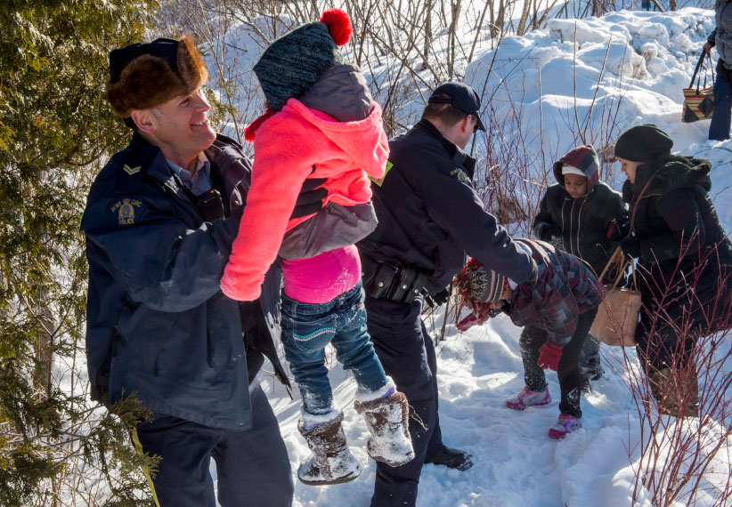 Family members from Somalia are helped into Canada by RCMP officers along the U.S.-Canada border near Hemmingford, Que., on Friday, February 17, 2017. A number of refugee claimants are braving the elements to illicitly enter Canada. (Paul Chiasson/CP)