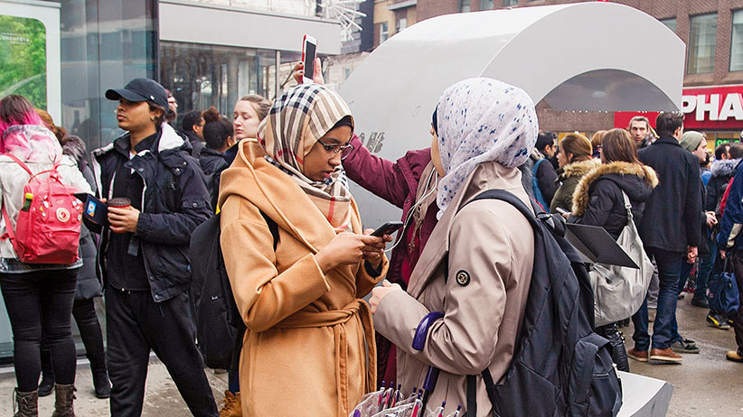 Muslim women check their cell phones outside Concordia University in Montreal, Wednesday, March 1, 2017, following a bomb threat. (Graham Hughes/CP)