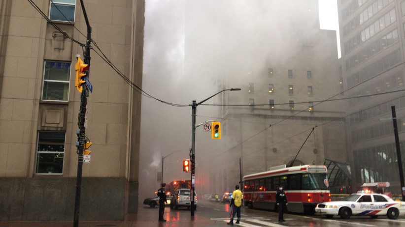 Smoke rises as police block off an intersection in the financial district after reports of a loud blast and heavy smoke could be seen in Toronto, Ontario, Canada May 1, 2017. (Jim Tanner/Reuters)