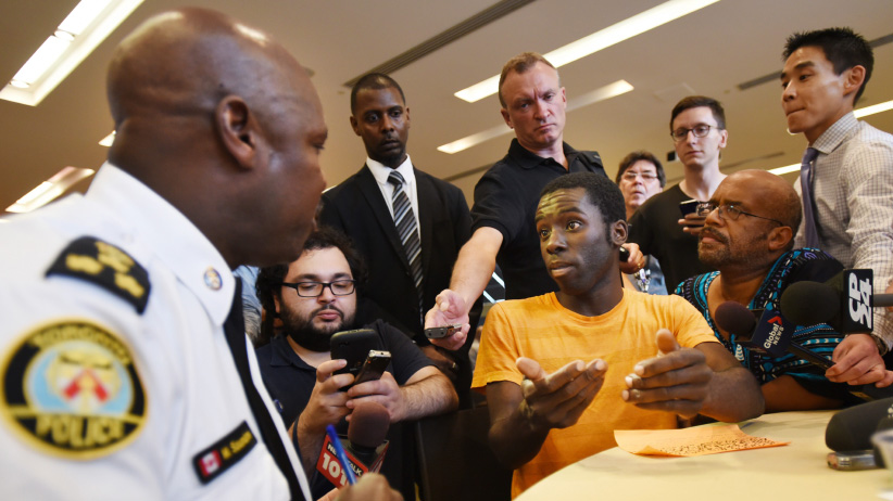 Writer Desmond Cole (right in orange shirt) puts questions to Chief Mark Saunders, Toronto Police Services (LEFT) during a public consultation on street checks in Toronto to receive input and feedback from Ontarians. (Fred Lum/The Globe and Mail/CP))