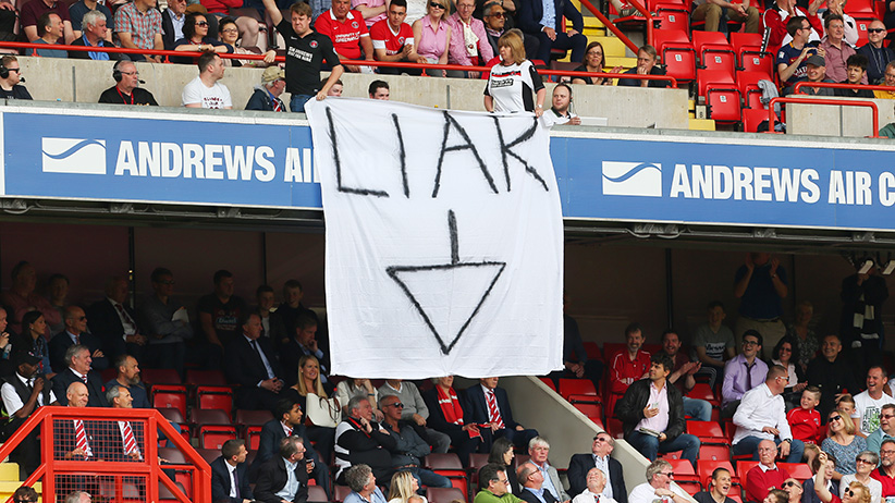 "Charlton Athletic fans hold a banner saying ""Liar"" and an arrow pointing to the directors box in protest against Roland Duchatelet owner of Charlton Athletic during the Sky Bet Championship match between Charlton Athletic and Burnley at The Valley on May 7, 2016 in London, United Kingdom. (Catherine Ivill/AMA/Getty Images)"