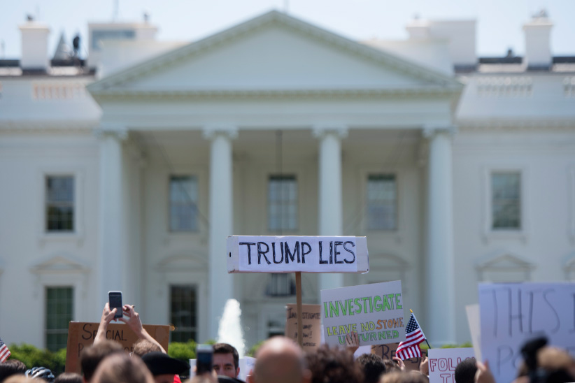 A protester holds a placard in front of the White House during a protest demanding an independent investigation in the Trump/Russia ties after the firing of FBI Director James Comey in Washington, DC, May 10, 2017. (Jim Watson/AFP/Getty Images)