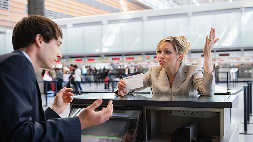 Upset businesswoman checking in at airport ticket counter. (Jupiterimages)