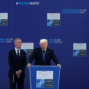 U.S. President Donald Trump speaks beside NATO Secretary General Jens Stoltenberg at the start of the NATO summit