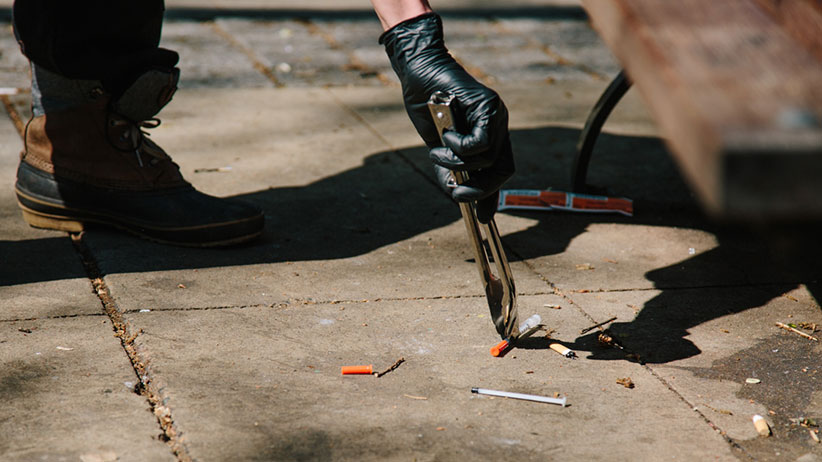 A used needle is picked up with tongs from the sidewalk in downtown Vancouver. (Photograph by Jackie Dives)
