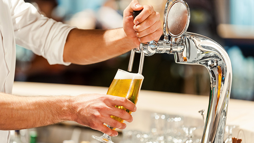 Pouring fresh beer. Close-up of young bartender pouring beer while standing at the bar counter (G-Stock Studio/Shutterstock)
