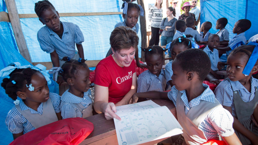 International Development Minister Marie-Claude Bibeau reads a learning manual to school girls where the school was reopened following the passing of hurricane Matthew, in Camp Perrin, Haiti, on Thursday, November 17, 2016. (Paul Chiasson/CP)
