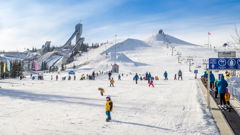 Calgary, Canada - March 1, 2015: People enjoying the skiing at Canada Olympic Park on March 1, 2015 in Calgary, Alberta. Visible are skiers at the base of the hill. Ski jump towers are on the top left.