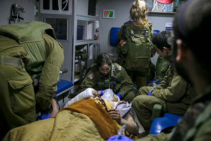 Israeli soldiers give initial medical treatment to wounded Syrians in an Israeli military ambulance, near the Syrian-Israeli border, in the Israeli-occupied Golan Heights January 18, 2017. Picture taken January 18, 2017. (Baz Ratner / Reuters)