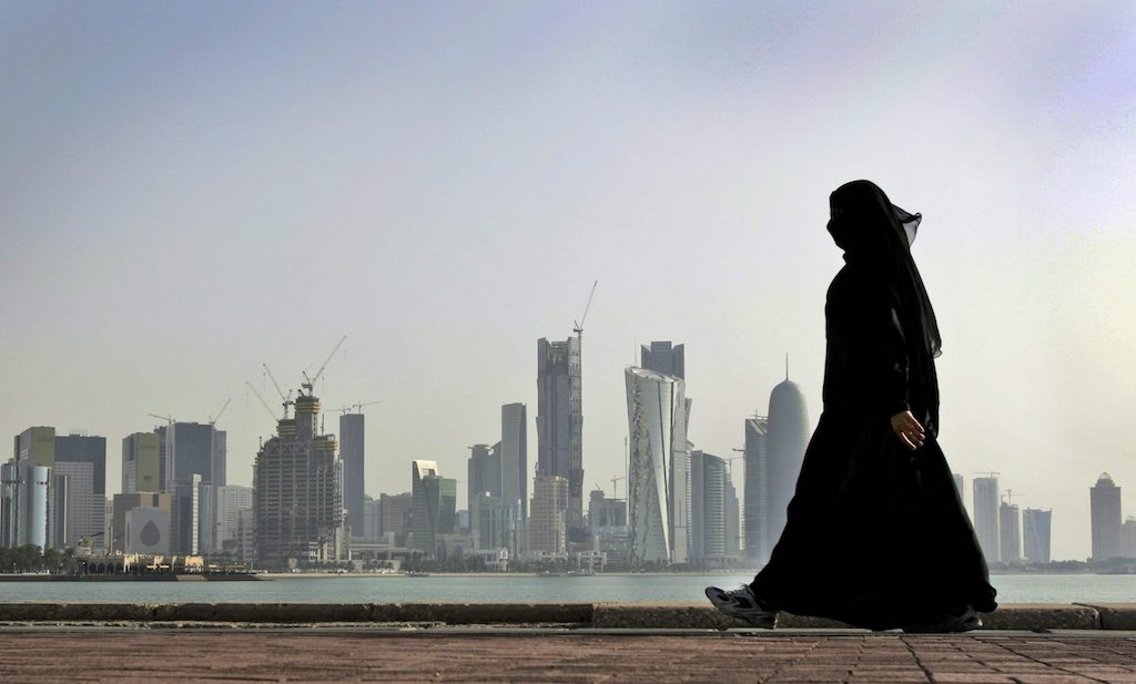 FILE- In this May 14, 2010 file photo, a Qatari woman walks in front of the city skyline in Doha, Qatar. A popular independent online news outlet in the Gulf nation of Qatar says its website has been blocked inside the country. The Doha News site said Thursday that Qatar's two internet service providers simultaneously blocked the site, suggesting they did so on order of government regulators. (AP Photo/Kamran Jebreili, File)