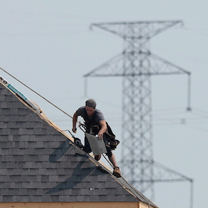 A construction worker shingles the roof of a new home in a development in Ottawa on Monday, July 6, 2015. Experts say measures introduced by the Ontario government to cool the red-hot housing market are likely to leave a lot of the buyers on the sidelines as they await to see the impact of the changes. THE CANADIAN PRESS/Sean Kilpatrick