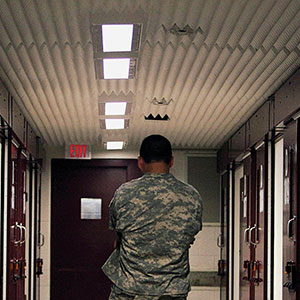 A U.S. soilder stands inside a hallway at Camp 5 detention facility on May 31, 2009 at U.S. Naval Base Guantanamo Bay, Cuba. Camp six is a medium-security facility with the capability of holding in a maximum-security portion of its roughly 60 detainees, based on their compliance with rules, according to the U.S. military. Former child soldier Omar Khadr, the Canadian citizen captured on the battlefield in Afghanistan in 2002 is expected to appear in a military commission hearing tomorrow with the charge of providing support to terrorism after allegedly throwing a grenade that killed a US soldier. This trial marks the first hearing of the Bush-era war crimes tribunals to take place under U.S. President Barack Obama.  (Brennan Linsley/Getty Images)