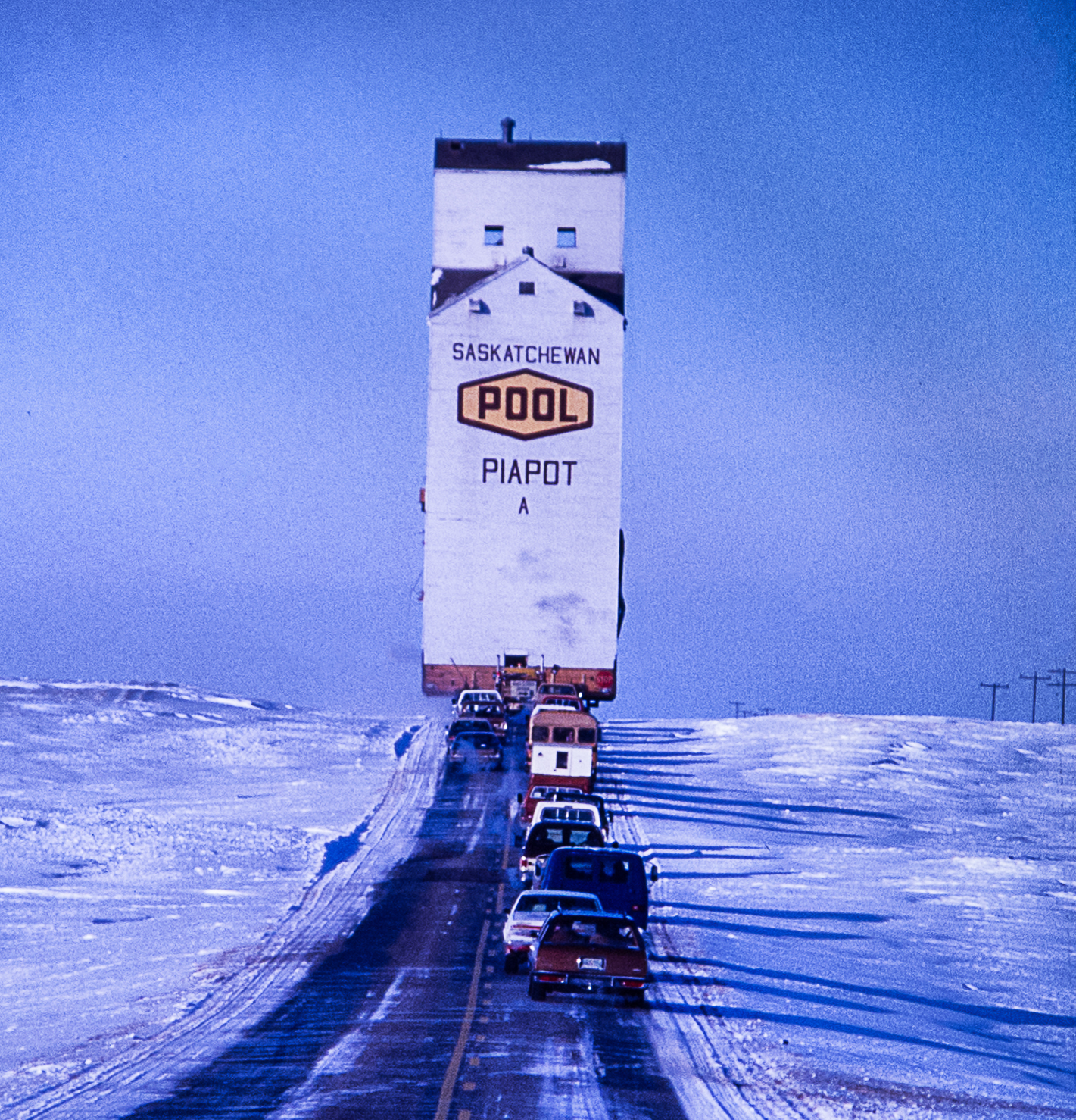 I took these photos in January, 1979. On a road trip in southwestern Saskatchewan (on highway 21 between Maple Creek and Fox Valley) I came across this unusual scene. Once an icon of the prairie, the grain elevator has nearly been eliminated, but seeing one being moved on a very cold day in winter will not likely happen again. It was a bitterly cold minus 30, just as an aside.