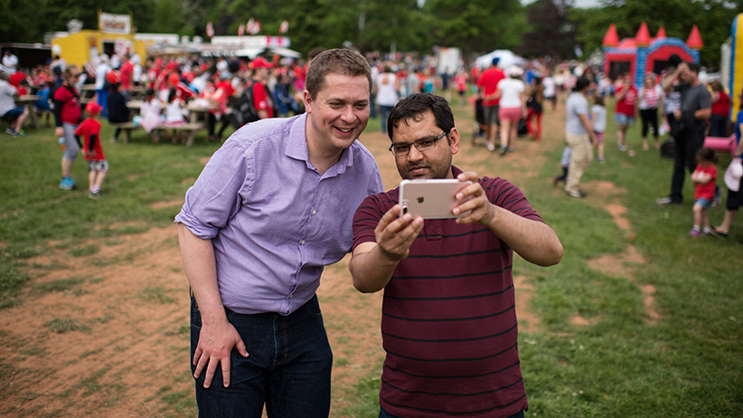 Conservative Party Leader Andrew Scheer, left, takes a selfie with a supporter during Canada Day festivities in Charlottetown, P.E.I. on Saturday, July 1, 2017. (Photograph by Darren Calabrese)