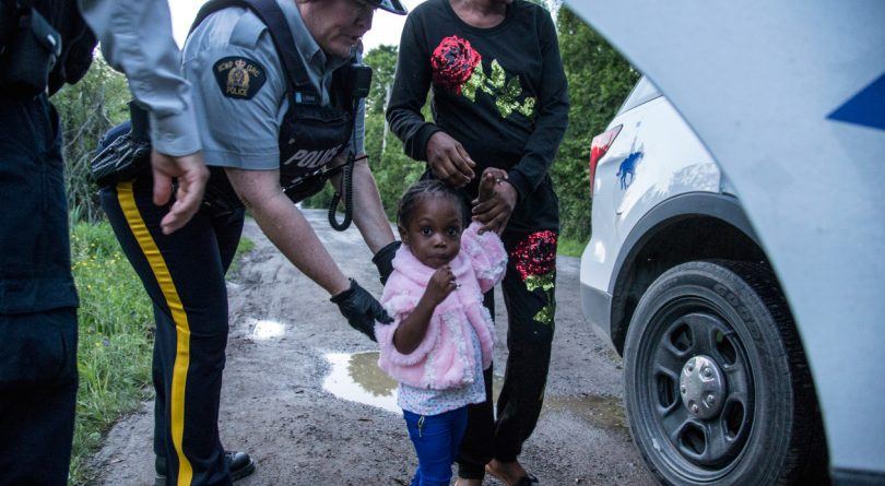 A woman and child being led to a police car