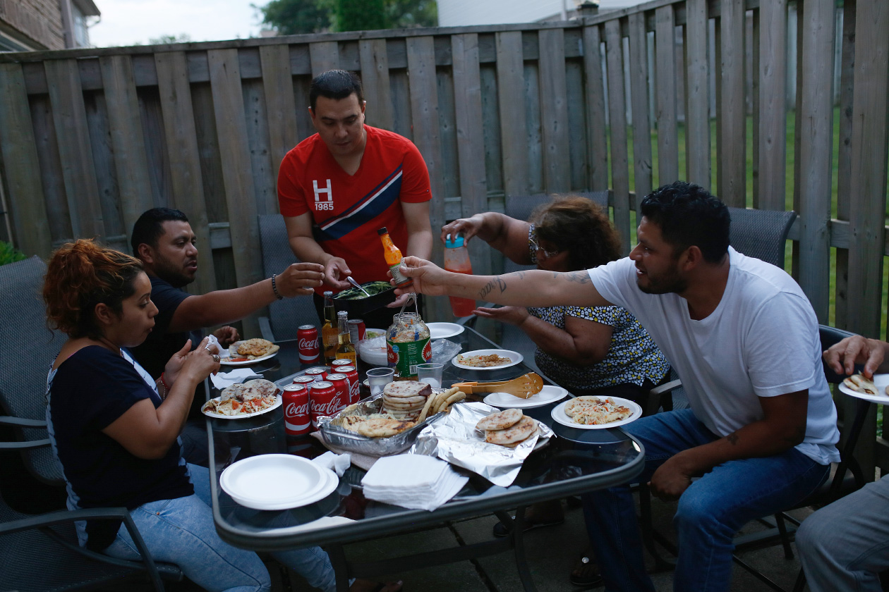 Jenny Vásquez, Jorge Cisco, Mauricio Espinosa, Marina de Cisco and Pablo Vásquez sit down to eat together outside the house in London, Ontario.