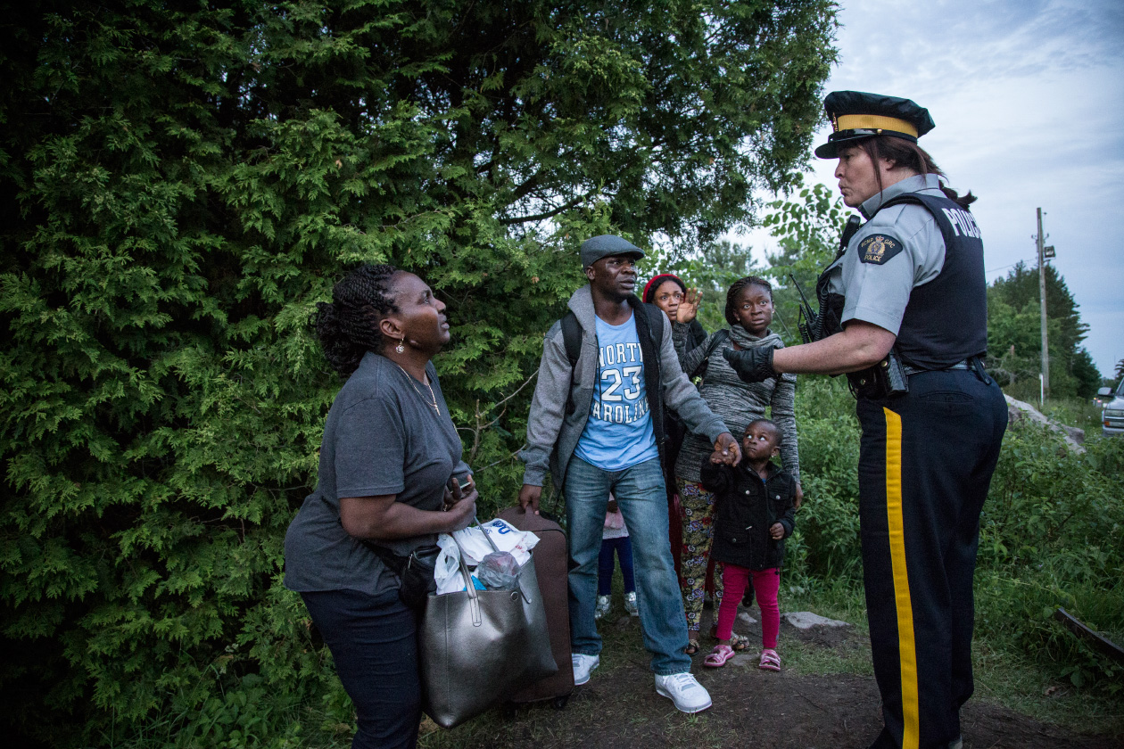 A group of seven people from Nigeria are informed by an RCMP officer of their rights and the law that they are breaking by crossing illegally from the USA into Canada at Roxham Rd. Quebec. (Photograph by Roger LeMoyne)