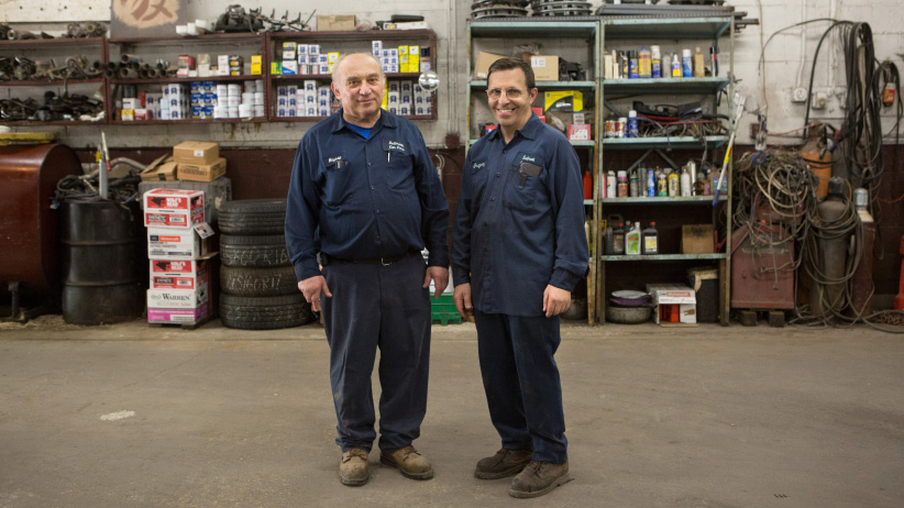 Moysey Zhuravel, nicknamed Misha, left, poses for a portrait with colleague Gregory Bevsky, nicknamed Grisha, at the Sudbrook Car Care Center in Pikesville, Maryland, July 3, 2017. Misha came to the U.S. from Belarus in 1990 and says that he has been in the car repair industry most of the time since then. Grisha immigrated from Ukraine in 2003. (Photograph by Allison Shelley)