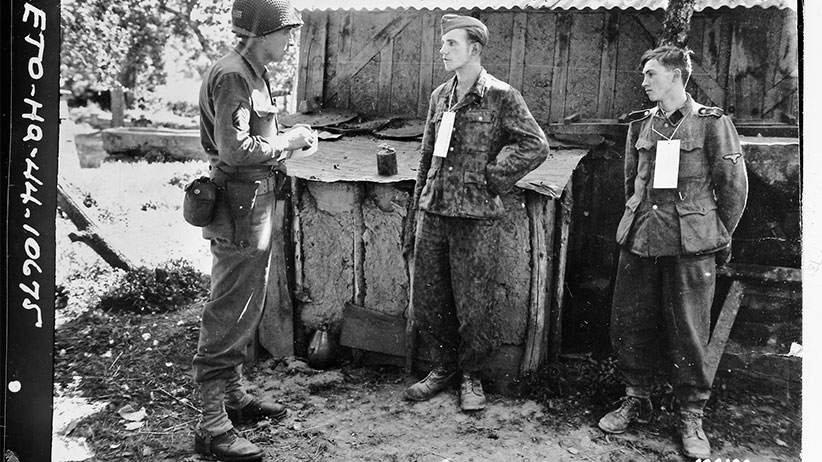 Martin Selling questions German prisoners near the front in France, 1944. (U.S. Army Signal Corps)
