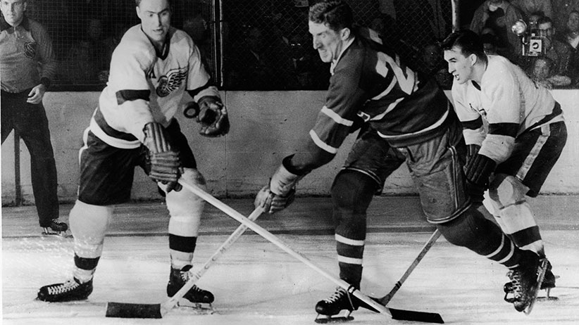 Canadian hockey player Red Kelly (left) of the Detroit Red Wings battles with Paul Masnick of the Montreal Canadiens for an airborne puck while Red Wing Marty Pavelich (right) skates in to join the action during the final game of the Stanley Cup in Detroit, Michigan, April 16, 1954. Detroit went on to win the game and the Cup. (Bruce Bennett Studios/Getty Images)