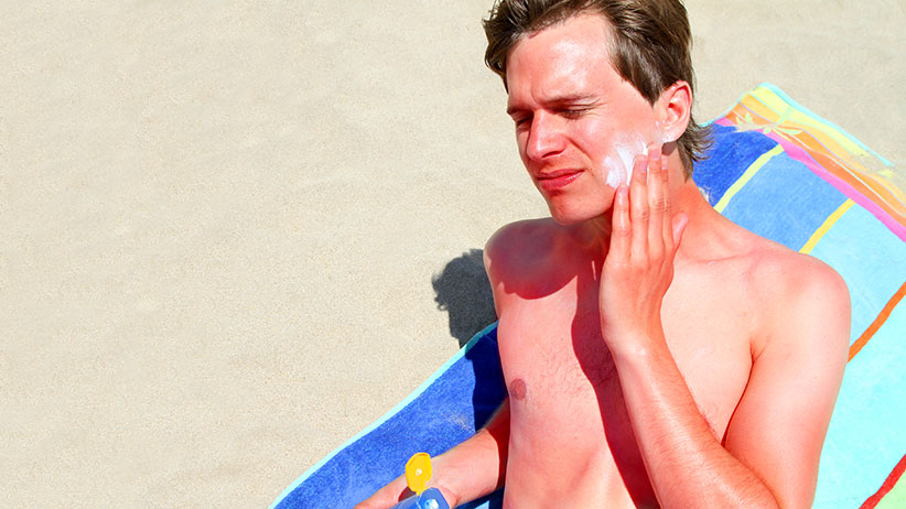 Sunburnt adult male applies sun lotion to face on beach, while lying on beach towel. (Tom And Steve/Getty Images)