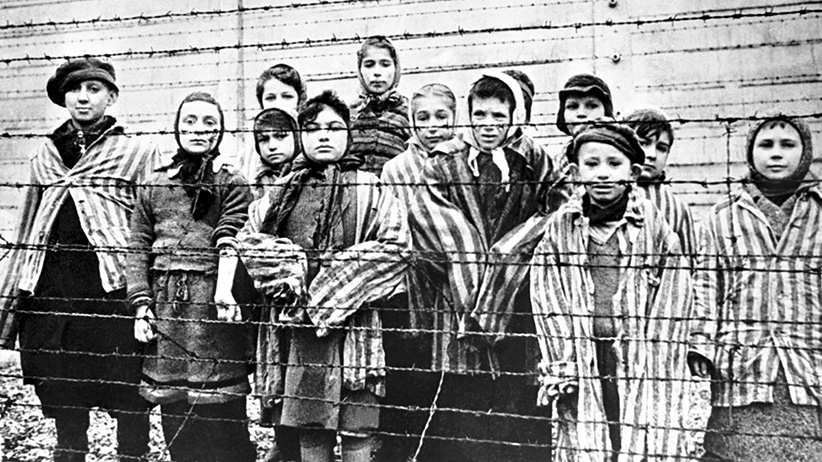 A group of child survivors behind a barbed wire fence at the Nazi concentration camp at Auschwitz-Birkenau in southern Poland. (Alexander Vorontsov/Galerie Bilderwelt/Getty Images)
