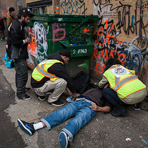 Staff members from the popup safe injection tent prepare the insect a man with Naloxone as he overdoses in a Downtown Eastside alley in Vancouver, British Columbia, November 18, 2016. (Rafal Gerszak)