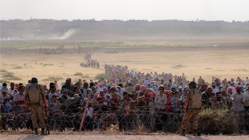 Syrians fleeing from clashes between the Islamic State of Iraq and Levant (ISIL) militants and Democratic Union Party (PYD) forces in the Ar-Raqqah Governorate of Syria, wait at the Turkish-Syrian border to cross into Turkey on September 18, 2014 near Turkey's Sanliurfa province. (Halil Fidan/Anadolu Agency/Getty Images)