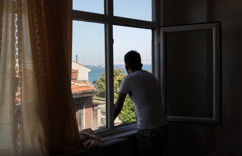 In Istanbul, Turkey, Ahmed Stanekzai (not his real name) looks out over the Marmara sea from his apartment in Istanbul. Since January, Stanekzai has been trying to come to Canada, something he has dreamed about since seeing the video of Prime Minister Justin Trudeau welcoming refugees at Toronto's Pearson International airport in December 2015. The demand to come to Canada has spiked in recent years, far outpacing the Liberal government's refugee quotas. The winners are smugglers and scammers who cash in on people's dreams. (Photograph by Adnan R. Khan)