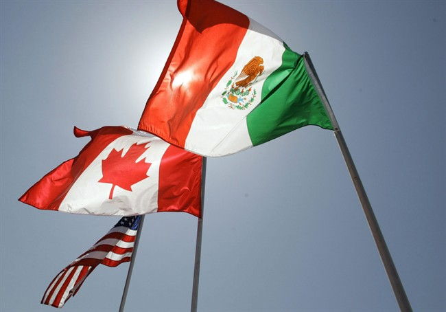 In this April 21, 2008 file photo, national flags of the United States, Canada, and Mexico fly in the breeze in New Orleans. Negotiations start Wednesday for an update to the quarter-century-old North American Free Trade Agreement. THE CANADIAN PRESS/AP/Judi Bottoni