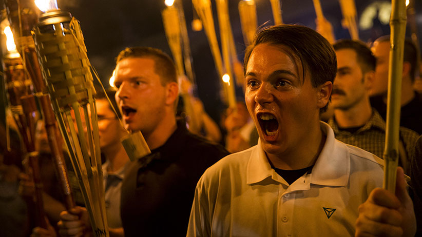 Peter Cvjetanovic (R) along with Neo Nazis, Alt-Right, and White Supremacists encircle and chant at counter protestors at the base of a statue of Thomas Jefferson after marching through the University of Virginia campus with torches in Charlottesville, Va., USA on August 11, 2017. (Samuel Corum/Anadolu Agency/Getty Images)