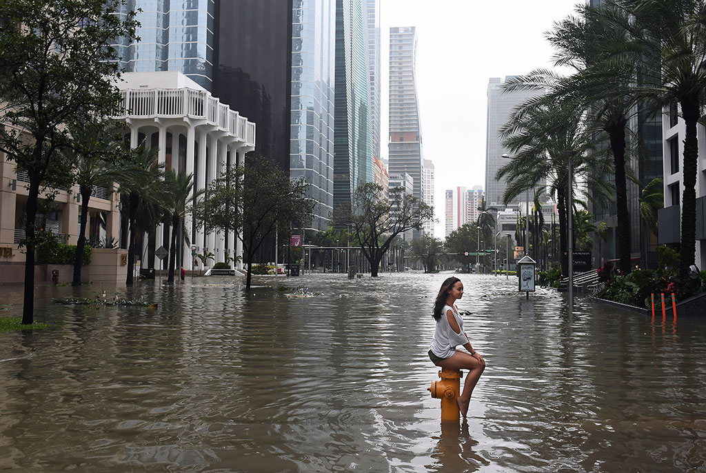 Mia Herman has an acquaintance take a photo of her sitting on a fire hydrant on a flooded street as Hurricane Irma hits the area on Sunday September 10, 2017 in Miami, FL. (Matt McClain/The Washington Post/Getty Images)